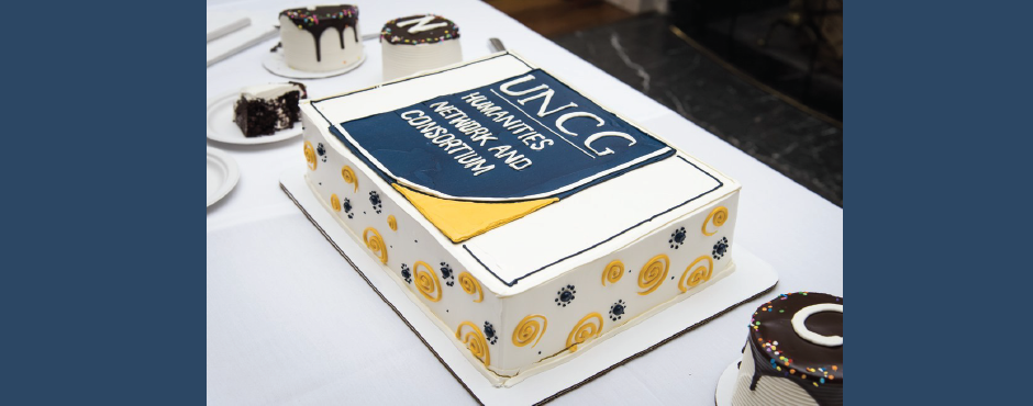 "A photo of a rectangular cake. It is mostly white, with blue and gold spirals on the sides, with a blue and gold square on top that reads ""UNCG: Humanities Network and Consortium"" in white letters."